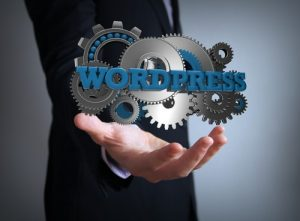 text wordpress with gears over businessman hand